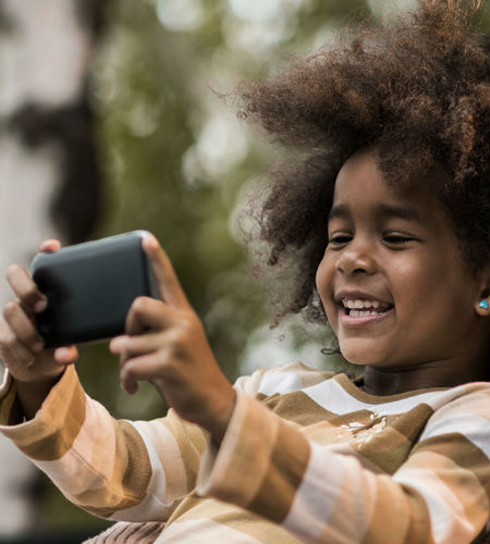 Young girl looking at smartphone and smiling